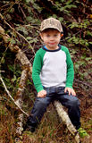 Boy Child with Camo Hat. A closeup of an adorable 4 year old boy child with a chubby face, wearing a camo bill cap, sitting on a tree branch. Shallow depth of royalty free stock photo