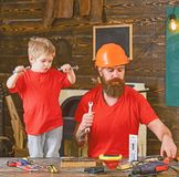 Boy, child cheerful holds bolts or screws, having fun while handcrafting with dad. Father, parent with beard in helmet. Teaching son to use different tools in royalty free stock photos