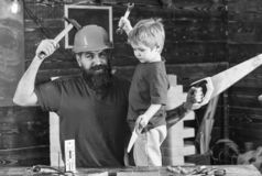 Boy, child cheerful holds toy saw, having fun while handcrafting with dad. Father, parent with beard in protective. Helmet teaching son to use different tools stock image