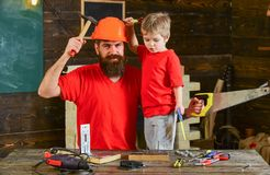 Boy, child cheerful holds toy saw, having fun while handcrafting with dad. Fatherhood concept. Father, parent with beard. In protective helmet teaching son to Royalty Free Stock Photos