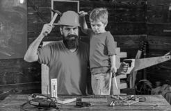 Boy, child cheerful holds toy saw, having fun while handcrafting with dad. Fatherhood concept. Father, parent with beard stock photography