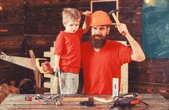 Boy, child cheerful holds toy saw, having fun while handcrafting with dad. Fatherhood concept. Father, parent with beard. In protective helmet teaching son to stock photo