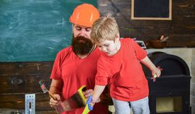 Boy, child cheerful playing with toy saw, learning use tools with dad. Father, parent with beard in protective helmet. Teaching little son to use different Royalty Free Stock Photos