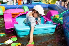 Boy child collecting toy fish in plastic boat royalty free stock photo