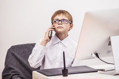 Boy child with a computer, in the office in a white shirt busine. Ssman. Studio, technology, monitor, ideas, communication Royalty Free Stock Photos