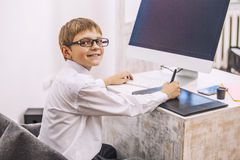 Boy child with a computer, in the office in a white shirt busine Stock Image