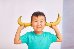 Boy child covered his ears with bananas royalty free stock image