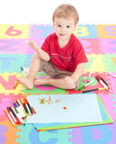 Boy child drawing on kids mat. Young boy child drawing on kids alphabet mat. Isolated on white royalty free stock photography