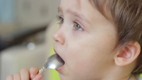 Boy child eating food with a spoon. The face of the child is close-up stock video footage
