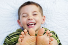 Boy child face bare feet toes Royalty Free Stock Image