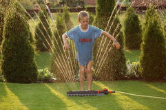 Boy child and garden sprinkler 3. Boy child playing with the garden sprinkler stock images