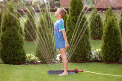 Boy child and garden sprinkler1. Boy child playing with the garden sprinkler stock image