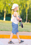 Boy Child going with Skateboard behind view Outdoor Stock Photography