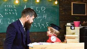 Boy, child in graduate cap looks at scribbles on chalkboard while teacher explains. Individual lesson concept. Teacher. With beard, father teaches little son in stock image