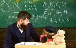 Boy, child in graduate cap looks at scribbles on chalkboard while teacher explains. Individual lesson concept. Teacher. With beard, father teaches little son in royalty free stock image