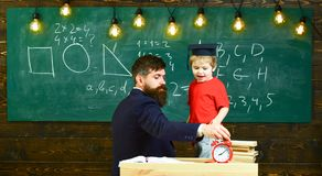 Boy, child in graduate cap play with dad, having fun and relaxing during school break. School break concept. Teacher. With beard, father teaches little son in Stock Images