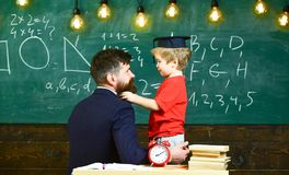 Boy, child in graduate cap play with dad, having fun and relaxing during school break. Teacher with beard, father. Teaches little son in classroom, chalkboard royalty free stock images