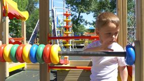Boy child with great pleasure calculates the rings on the playground. The boy with great pleasure calculates the rings on the playground. Slow motion stock video