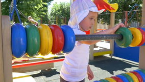 Boy child with a great pleasure finds the rings on the playground stock footage