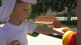 Boy child with great pleasure recounts rings on the playground. Slow motion stock footage