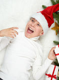 Boy child having fun with christmas decoration, face expression and happy emotions, dressed in santa hat, lie on white fur backgro Royalty Free Stock Image