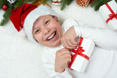 Boy child having fun with christmas decoration, face expression and happy emotions, dressed in santa hat, lie on white fur backgro Stock Photos