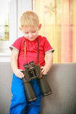 Boy child kid playing with binoculars. At home. Royalty Free Stock Photography