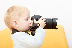 Boy child kid playing with camera taking photo. At home. Royalty Free Stock Images