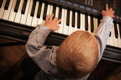 Boy child kid playing on digital keyboard piano synthesizer Stock Photos
