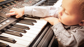Boy child kid playing on digital keyboard piano synthesizer Royalty Free Stock Image