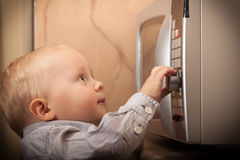 Boy child kid playing with timer of microwave oven Royalty Free Stock Photos