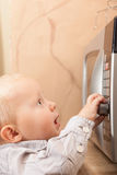 Boy child kid playing with timer of microwave oven Stock Photography