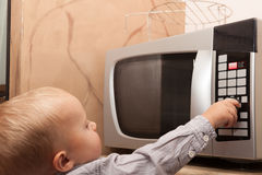 Boy child kid playing with timer of microwave oven stock image