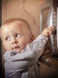Boy child kid playing with timer of microwave oven Royalty Free Stock Photo