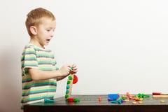Boy child kid preschooler playing with building blocks toys interior Stock Photos