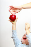 Boy child kid reaching for apple fruit. At home. Royalty Free Stock Photos