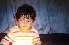 Boy child looking down on glow of light. Small indian asian boy child with curly hairs looking down on glow of light with curiousity and his eyes are shining Stock Photos