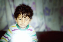 Boy child looking down on glow of light. Small indian asian boy child with curly hairs looking down on glow of light with curiousity and his eyes are shining Royalty Free Stock Image