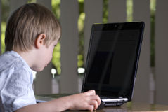 Boy child looking at laptop screen Royalty Free Stock Photos