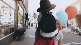 Boy child on mom`s shoulders, two air balloons. Mother and son in hat with backpack walk together along the street. 4K. Boy child on mom`s shoulders, two air stock video footage