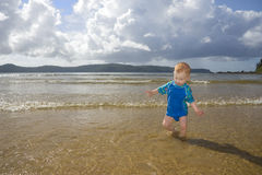 Boy child playing in fun beach water waves. Toddler playing at beach in sunlight with impending storm Stock Photo