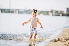 Boy child playing makes splashes, beats hands on the water in the river at sunset. Of the day stock images