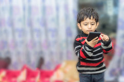Boy child playing with mobile phone Stock Images