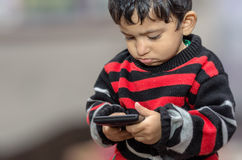 Boy child playing with mobile phone Royalty Free Stock Photography