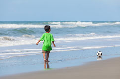 Boy Child Playing Soccer Football on Beach. Boy male child, playing football soccer alone and having fun in the sand on a sunny beach Royalty Free Stock Image