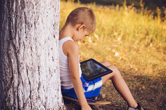 Boy Child playing with Tablet PC Outdoor Stock Photos