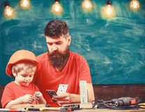 Boy, child in protective helmet makes by hand, repairing, does crafts with dad. Father as handyman concept. Father. Parent with beard and little son in royalty free stock photos