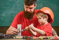 Boy, child in protective helmet makes by hand, repairing, does crafts with dad. Father with beard and little son in. Classroom teaching to use tools, chalkboard stock photo
