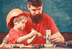 Boy, child in protective helmet makes by hand, repairing, does crafts with dad. Father with beard and little son in stock image