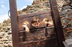 Boy child put in the stocks at exhibition royalty free stock photo